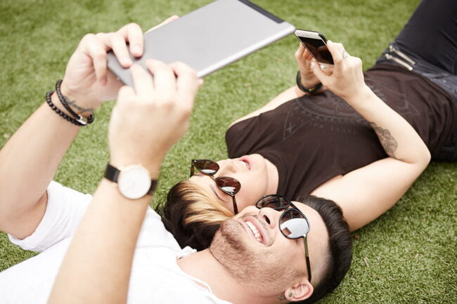 Man and woman laying in grass looking at tablets together
